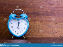 heart-shaped-alarm-clock-wooden-background-twelth-o-time-149382347